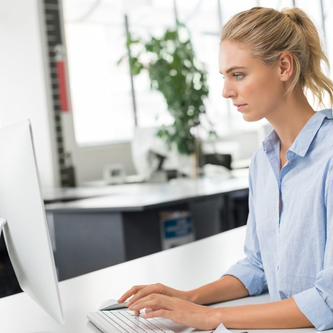 Young woman working in office sitting at desk. Beautiful blonde businesswoman typing and writing a email on computer. Young assistant completing pending work in office.